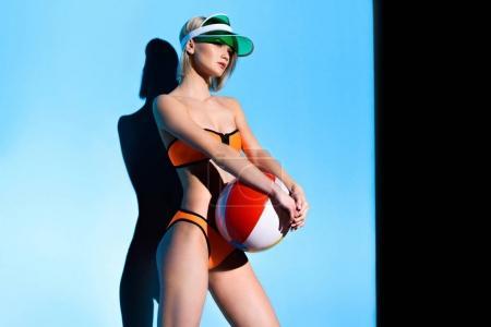 beautiful girl posing in bikini and sun visor with beach ball on blue