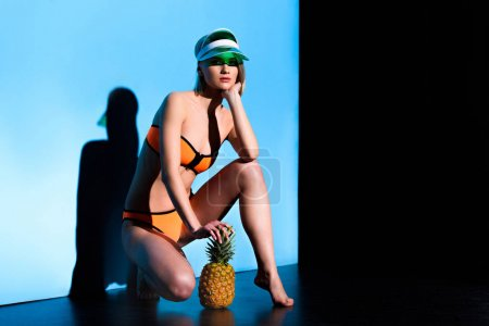 attractive girl posing in swimsuit and sun visor with pineapple on blue