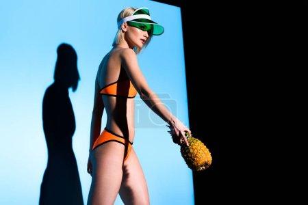 slim caucasian girl posing in bikini and sun visor with pineapple on blue