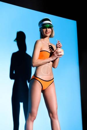 attractive girl posing in swimsuit and sun visor with coconut cocktail on blue