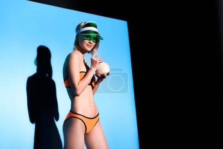 beautiful girl posing in bikini and sun visor with coconut cocktail on blue