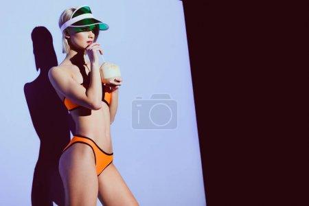 fashionable girl in bikini and sun visor drinking coconut cocktail on purple