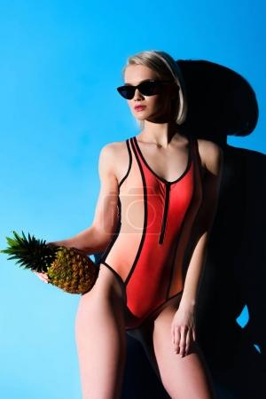 slim girl posing in swimsuit and sunglasses with pineapple, on blue