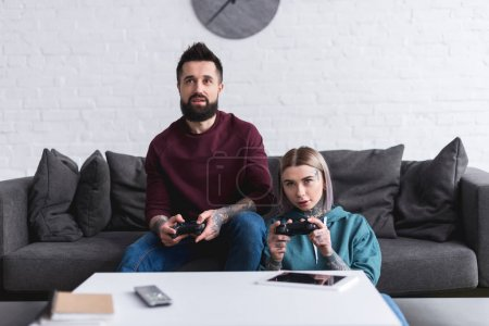 serious tattooed couple playing video game at home