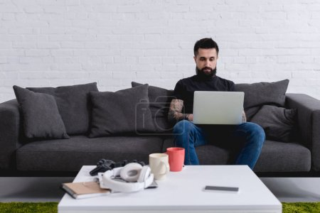 tattooed handsome man using laptop on sofa at home