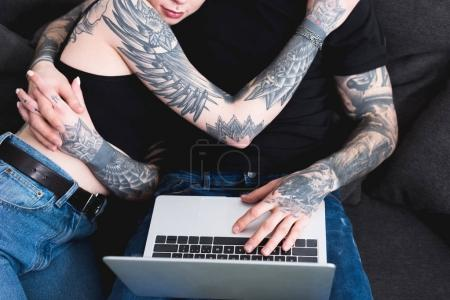 cropped image of tattooed couple using laptop