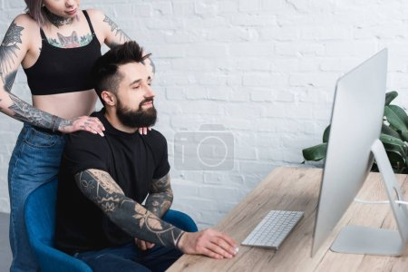 cropped image of tattooed girlfriend touching boyfriend near table with computer at home