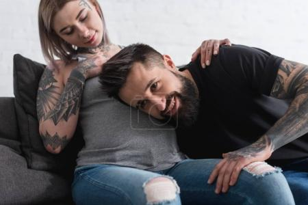 tattooed boyfriend listening abdomen of pregnant girlfriend at home