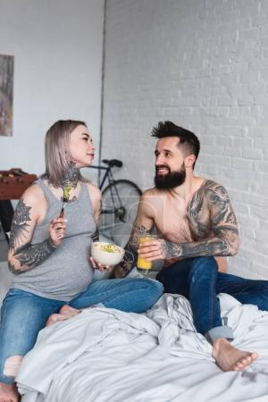 pregnant tattooed girlfriend eating salad at home