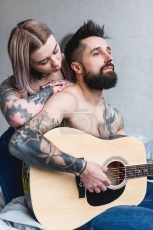 boyfriend playing guitar for tattooed girlfriend at home