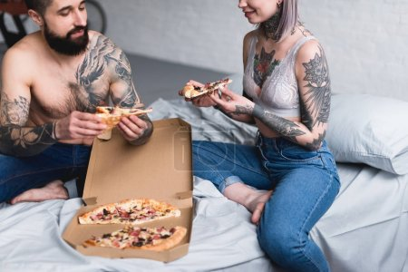 cropped image of tattooed couple eating pizza at home