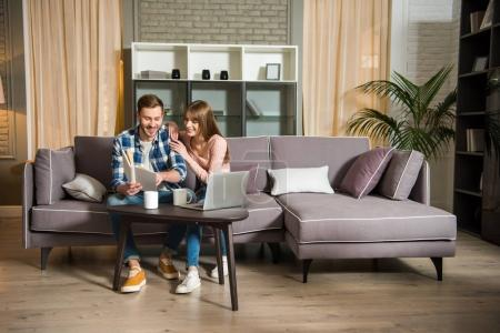 Jeune couple assis sur le canapé et la lecture de livre dans le salon