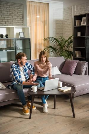Foto de Vista frontal de la sonriente pareja en sofá con ordenador portátil en la acogedora sala de estar - Imagen libre de derechos