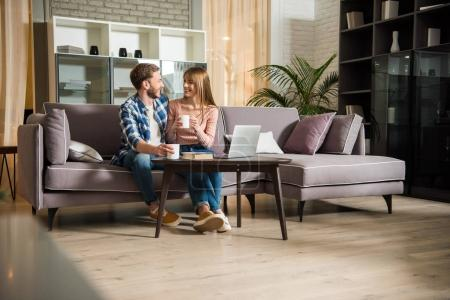 Photo for Young couple sitting on couch with cups in living room with modern design - Royalty Free Image
