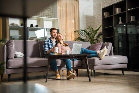 Foto de Vista nivel superficie de pareja viendo el portátil en la sala de estar con interior moderno - Imagen libre de derechos