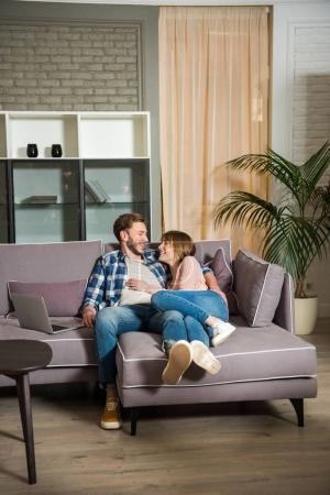 Foto de Pareja joven acostado en el sofá en sala de estar moderna - Imagen libre de derechos