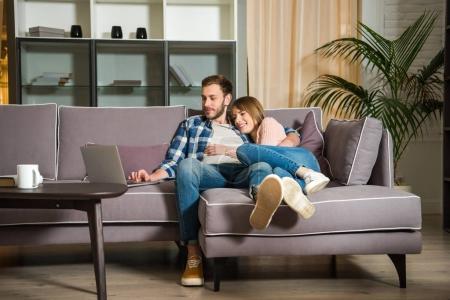 Foto de Novio abrazando mujer mientras él utilizando la computadora portátil en la sala de estar con diseño moderno - Imagen libre de derechos