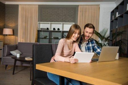 Foto de Pareja feliz en mesa con ordenador portátil y tableta digital en sala de estar con interior de diseño - Imagen libre de derechos