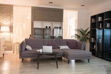 Photo for Interior of living room with couch, laptop at table and closet in modern design - Royalty Free Image