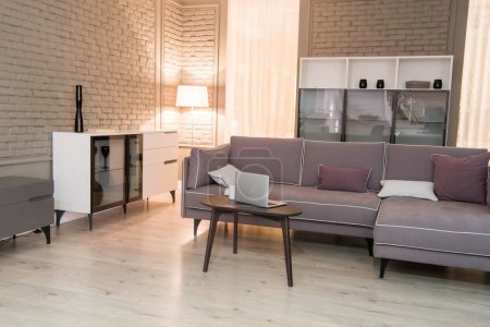 Interior of cozy living room with couch and laptop on table