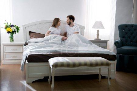 Foto de Pareja de mentira debajo de la manta en el acogedor dormitorio con un diseño moderno - Imagen libre de derechos