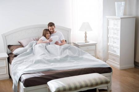 Couple having fun with digital tablet in bedroom with modern interior