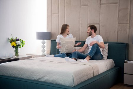 Young female holding pillow and talking to her boyfriend in modern bedroom