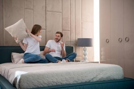 Woman going to hit her boyfriend by pillow in cozy bedroom