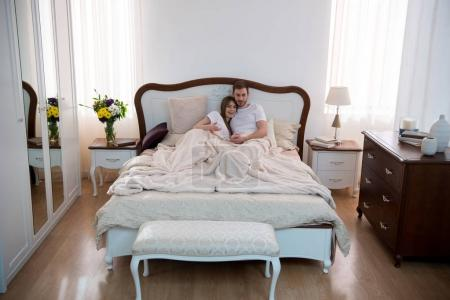 High angle view of happy couple hugging in cozy modern bedroom