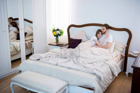 Couple lying on bed in cozy modern bedroom