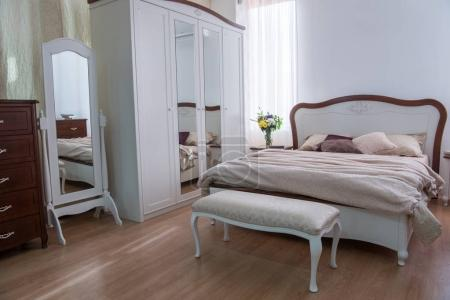 Interior of cozy bedroom with closet, bed and mirrors in modern design