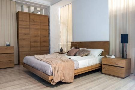 Interior of cozy modern bedroom with closet and bed