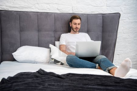 Front view of young man sitting on bed and using laptop in modern bedroom