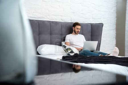 Surface level view of young man sitting on bed with laptop in modern bedroom