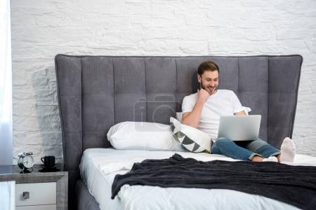 Photo for Happy young male using laptop in cozy modern bedroom - Royalty Free Image