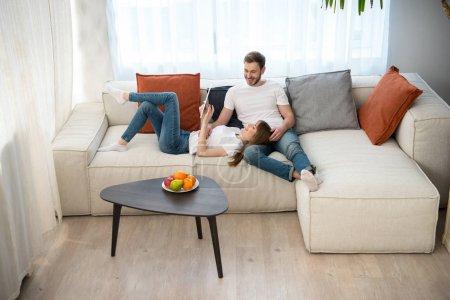 Femme à l'aide de tablette numérique et couché sur ses genoux de copain dans moderne moderne
