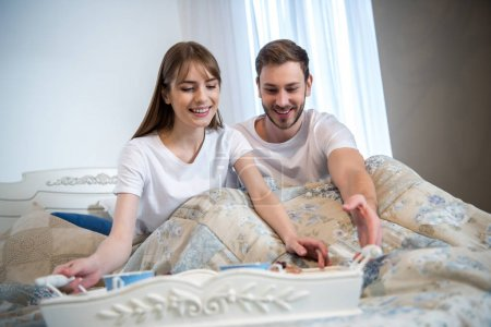 Couple in bed with breakfast on tray in modern bedroom