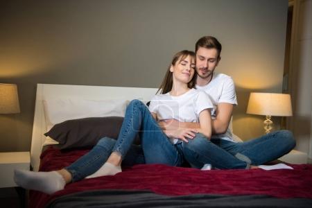 Male hugging his girlfriend in cozy modern bedroom