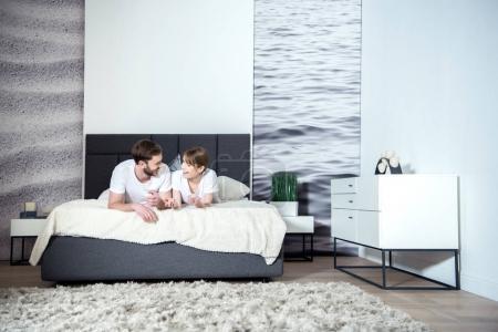 Foto de Sonriente pareja hablando y acostado en cama en acogedor dormitorio con interior moderno - Imagen libre de derechos