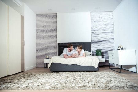 Young couple lying in bedroom with modern interior