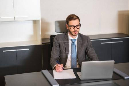 Front view of businessman sitting at table with laptop and holding pen in hand