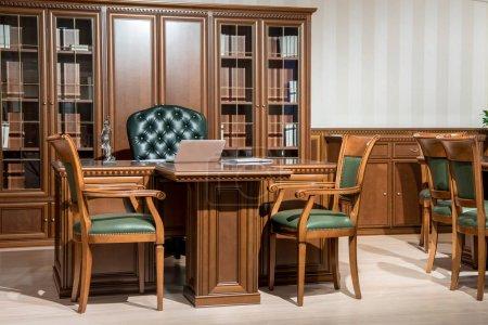 Photo pour Intérieur de la salle de bureau avec ordinateur portable sur une table en bois dans un design classique et chaises - image libre de droit