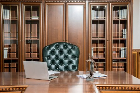 Photo for Interior of office room with laptop, statuette and papers on table - Royalty Free Image