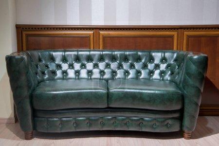 Photo pour Canapé en cuir vert en face du mur avec décoration en bois - image libre de droit
