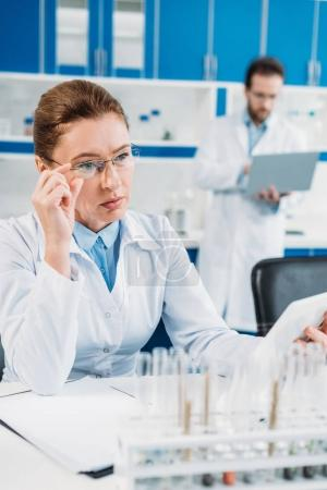 selective focus of female scientist using tablet at workplace with colleague behind in lab