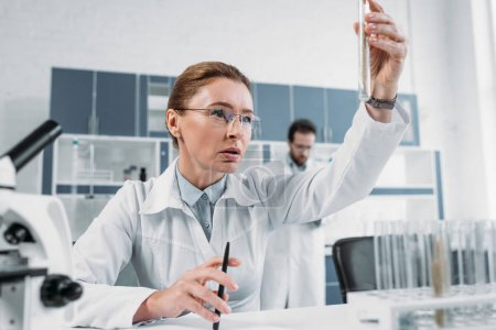 selective focus of female scientist looking at tube with reagent in hand with colleague behind in lab