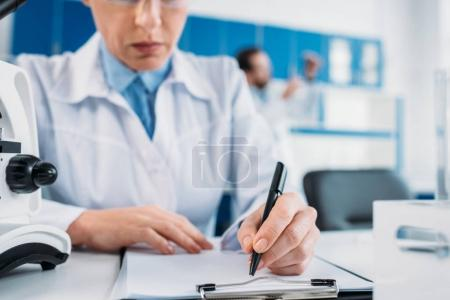 partial view of female scientist making notes in notepad at workplace with colleague behind in lab