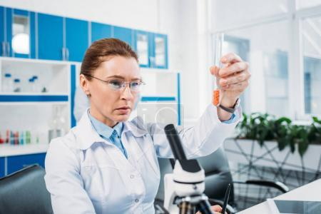 Photo for Portrait of focused female scientist in lab coat looking at tube with reagent in hand in laboratory - Royalty Free Image