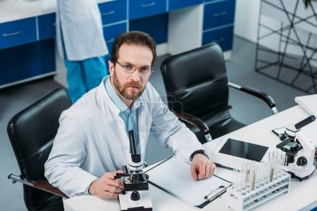 high angle view of scientist in white coat at workplace with microscopes in laboratory