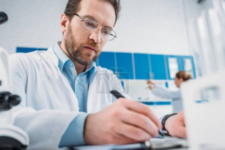 Photo for Selective focus of scientist in white coat and eyeglasses making notes in notepad at workplace in laboratory - Royalty Free Image